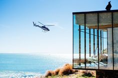 This isolated, oceanfront cottage throws you into luxury boasting incredible views through the glass walls and close to Christchurch, New Zealand. Christchurch New Zealand, Formal Gardens, Small Trees, Planting Flowers, Flowering Plants, Holiday Travel, Evergreen, Scenery, Around The Worlds