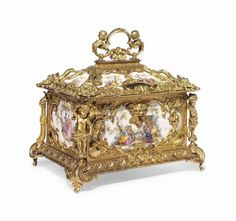 A FRENCH ORMOLU AND PORCELAIN JEWEL CASKET >LATE 19TH CENTURY<br>Inset with panels of courting couples against a white ground, the rectangular hinged lid surmounted by a handle cast with caryatid putti, cornered by flower-filled cornucopia, the interior lined with blue silk, the body decorated with foliate scrolls and cartouches, the front angles cast with cherubs, on scrolled feet >15 in. (38 cm.) high; 15 in. (38 cm.) wide; 10.12 in. (26.5 cm.) deep