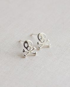 Small skull and crossbones earrings have a unique screaming skull. These cute and funny little stud earrings are available in gold and silver. By Olive Yew.
