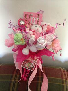 Baby Girl Shower Bouquet. Rolled up onesies, hats, socks, etc. on skewers in a vase.  Take a photo of the items beforehand and attach to vase.  I used part of the invitation as a card.