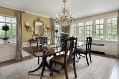Upscale home with a dining room wing.  White wood paneling scales up half-way on the walls followed by beige paint.