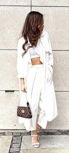 A white duster coat, crop top, and white trousers