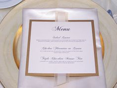 Simple white napkin fold, gold accented menu, gold charger