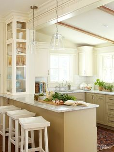 A built-in glass cabinet that faces the dining room makes a space-saving alternative to a freestanding china hutch. The cabinet stretches from peninsula to ceiling with two doors to accommodate accessories in a variety of sizes.
