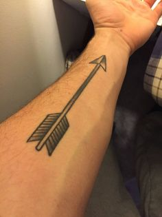 Tatuaje de una flecha en el antebrazo izquierdo.