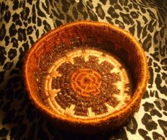 Floral design wool yarn coiled basket with gold and brown yarns created by Susan Richardson of Desert Mojo Designs.