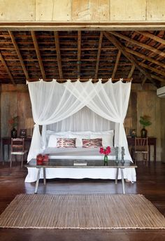 Suíte do chalé Madeira | O cortinado de filó sobre a cama realça os tons de palha e de madeira. Em frente a ela, esteira de palha (Foto: Evelyn Müller / Living Inside)