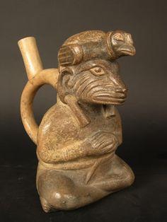 """Botella asa-estribo: """"Iguana"""" sentado con tocado de cóndor, orejeras, túnica y bulto en la espalda. Museo Larco, Lima – Perú / ML004122"""