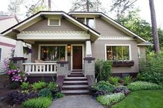 Love how the front of the homw is decorating with such lovely plant life. charming bungalow