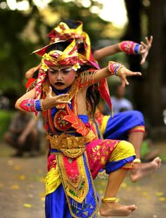 Balinese dancers in brightly coloured costumes.