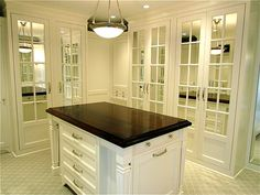 Elegant walk-in closet design with white closet island with wood countertop, floor to ...