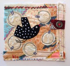 Black bird and blossom. Textile / fibre wall art collage. Original appliqué and embroidery on vintage crazy patchwork quilt