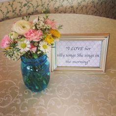 kitchen themed bridal shower - table decor fresh flowers and framed quote from groom about the bride