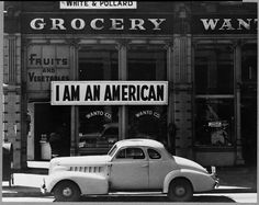 "PRINT AVAILABLE   Oakland, Calif., Mar. 1942. A large sign reading ""I am an American"" placed in the window of a store, at 13th and Franklin streets, on December 8, the day after Pearl Harbor. The store was closed following orders to persons of Japanese descent to evacuate from certain West Coast areas. The owner, a University of California graduate, will be housed with hundreds of evacuees in War Relocation Authority centers for the duration of the war"