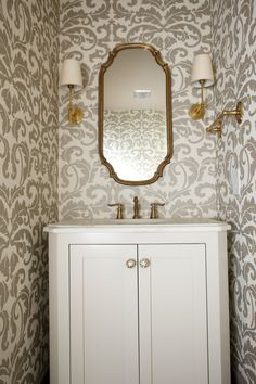 This powder room was updated with new wall paper and classic antique brass fixtures, creating a beautiful space.