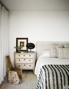 A guest bedroom is furnished with an antique wood stump chair, a Gustavian commode, a Saturne lamp by Serge Mouille, and a vase from Midland Shop.
