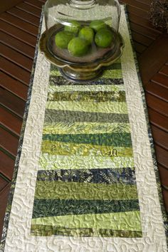 This is a handmade quilted table runner featuring strips in shades of green, leafy, woodsy prints. The strips are sewn crazy quilt or asymetrical style. The border is a warm cream colored print and the binding is a leafy batik print that matches the back as shown in the second picture. The quilt has tight machine stippling (my favorite part!) all throughout. The batting in the middle layer is 100% cotton. Finally, the binding is machine sewn on the front (which gets hidden) and hand sewn on…