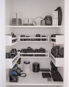 Coat closet turned photography equipment storage.  Shelves added, $3 spice racks from Ikea serve as storage for lenses and other gear.