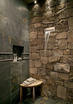 Stone wall shower with waterfall; Who would want to get out of the shower with this?