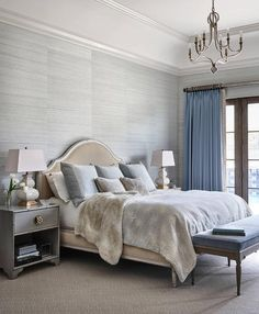 Gray and blue bedroom features walls clad in gray grasscloth wallpaper lined with French bed upholstered in camel colored fabric dressed in blue shams and a gray faux fur blanket flanked by gray bamboo nightstands and white Fang Gourd Lamps.