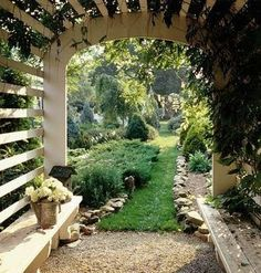 I love this garden arbor with interior benches and the stone lined soft grassy walkway.