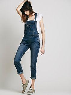 Washed Denim Overall | Distressed wash skinny denim overalls. 5-pocket style. Adjustable crisscross straps. Pocket detailing on front bib.