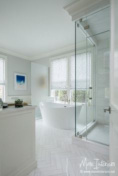 White and gray bathroom features a corner seamless glass shower filled with…