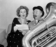 Greer Garson and Reginald Owen singing and playing tuba