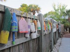 Decorate your fence with buoys: 27 Awesome Beach-Style Outdoor Living Ideas for Your Porch and Yard