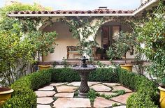 Spanish Colonial-style architecture dating back to 1933 gives this garden a classic feel. - Traditional Home®  Photo: Grey Crawford Design: Ruthie Sommers