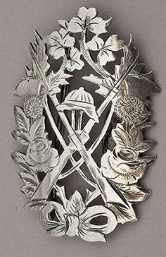 A Boer War silver belt buckle, with pith helmet above 2 crossed rifles with bayonets attached, surrounded by a wreath with the British national flowers (rose, thistle, shamrock and leek). The engraving is quite attractive. Unfortunately we have not been able to identify the regiment, we have seen nurse's buckles similar to this, but feel the presence of rifles makes a nursing attribution unlikely.