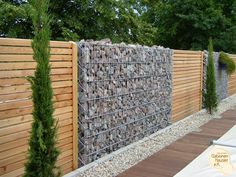 Gabion Wall Stone and Wood Fence. Along the fence line Backyard Fences, Fenced In Yard, Garden Fencing, Mesh Fencing, Garden Trellis, Gabion Retaining Wall, Outdoor Spaces, Outdoor Living, Gabion Baskets