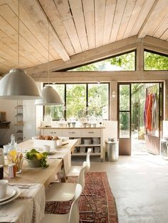 French country style kitchen. Concrete floors w/ warm wood ceiling