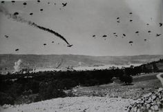 German paratroops landing on Crete, dropped from Junkers 52 transports, May 20,1941. Taken by a British combat photographer, the photo was edited for propaganda purposes to show a black smoke trail from a damaged Ju 52. Several were indeed lost by...