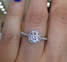 Make her fall in love all over again with this Tacori Petite Crescent Diamond Halo Engagement Ring Setting.  A soft string of accent diamonds glisten along this band, allowing your center diamond and blooming halo to shine bright.