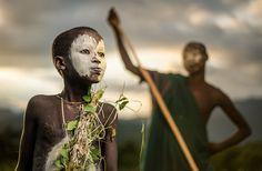 Impressionantes e Polêmicas fotos descrevem nossa raça humana - Menino da tribo nômade Suri da Etiópia com pinturas e acessórios tradicionais.