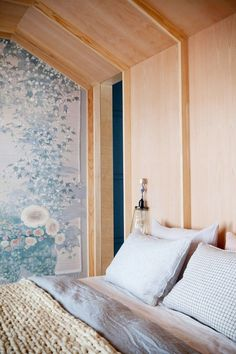Cozy bedroom with wooden architectural details, floral wallpaper, and pastel bedding