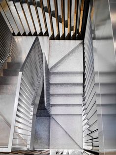 An aluminium foam staircase doglegs up the centre of Italian jewellery brand Repossi's flagship store, designed by Dutch architecture firm OMA on Paris' exclusive Place Vendôme.