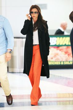 Victoria Beckham Photos - Victoria Beckham, wearing striking orange pants with a white top and black overcoat, seen arriving at JFK Airport in New York City. - Victoria Beckham Arrives in NYC Celebrity Look, Celebrity Dresses, Celebrity Travel, Celeb Style, New Hijab, Victoria Beckham Style, Inspirational Celebrities, Glamour, Everyday Fashion
