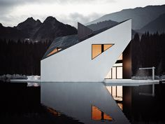 Rendered by graphic designer Michal Nowak, Crown House is a residence designed by 81.WAW.PL. Shaped like a crown, the home is characterized by the sharp lines that make up its exterior walls, their white color in stark contrast with the dark depths of the lake upon which it sits.          Renderings by: Michal Nowak