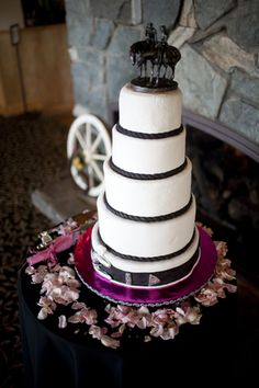 Five tier western styled cake with rope braid bands and a belt on the last tier with two horses and riders as a topper