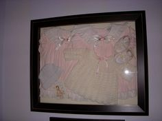shadow box of baby clothes