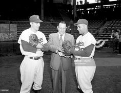 Catchers Rube Walker (left) and Roy Campanella (right) of the Brooklyn Dodgers pose with a representative of Wilson Sporting Goods (center) prior to a game at Ebbets Field in Brooklyn, New York in 1952.