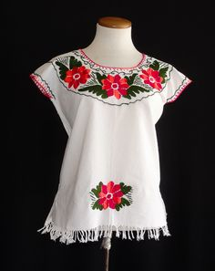 Hand-embroidered flowers in red and orange complement the neckline of this lovely jalapa blouse. Light-weight cotton manta is the perfect for a comfortable addition to any wardrobe. Sized x-small, fits size 2. Price: $34.00