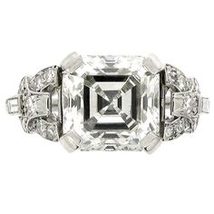 Art Deco diamond ring, circa 1920. A platinum ring set with one central square 4.01 ct Asscher cut diamond flanked by two rectangular baguette cut diamonds in rubover collet settings with an approx total weight of 0.14 carats, and fourteen round eight cut diamonds in bead settings with an approx total weight of 0.20 carats.