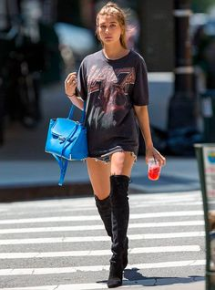 Look da modelo Hailey Baldwin com maxi t-shirt, short jeans e bota over the knee.