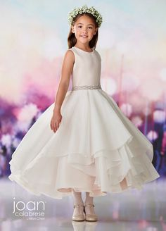 This Joan Calabrese 119391 ivory petal first communion dress features a satin bodice over a layered organza skirt, crowned with a beaded jewel neckline. A beaded waistband accents this sleeveless tea-length dress.