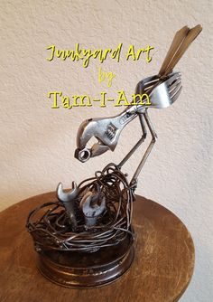 "Junkyard Art by Tam-I-Am. Three open-end wrenches, a crescent wrench, some flatware, and wire come together as ""A Mother's Love."" Repurposed tools, scrap metal art."