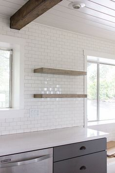 Thick natural wood floating shelves on subway tile