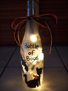 """Bottle of """"Boos"""" hand painted wine bottle with lights and black and orange bow...decorated with bats, ghosts and black cat... http://www.facebook.com/buggybeandesigns"""
